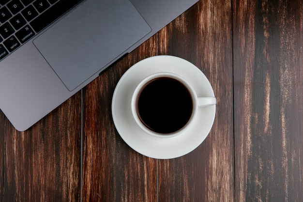 Draufsicht tasse tee mit laptop auf hölzernem hintergrund Kostenlose Fotos