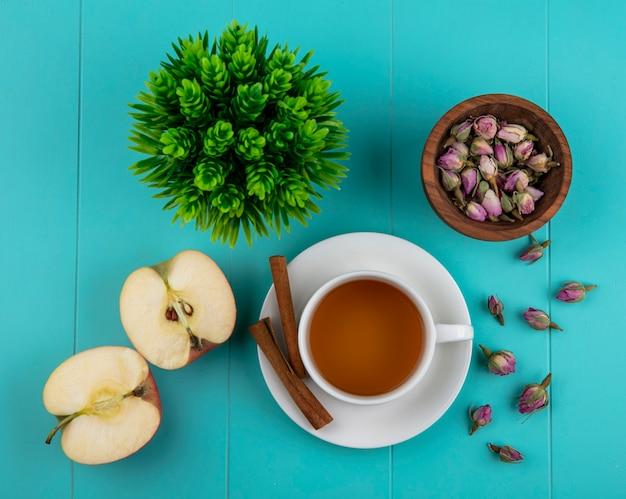 Draufsicht-tasse tee mit zimtgrünem apfel und trockenen rosenknospen auf einem blauen hintergrund Kostenlose Fotos