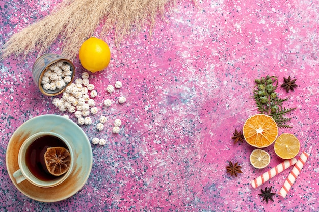 Draufsicht tasse tee mit zitrone und weißen süßen confitures auf rosa oberfläche Kostenlose Fotos