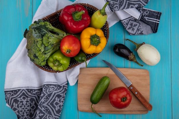 Draufsicht-tomate mit gurke auf schneidebrett mit messer und paprika mit brokkoli im korb und aubergine auf türkisfarbenem hintergrund Kostenlose Fotos