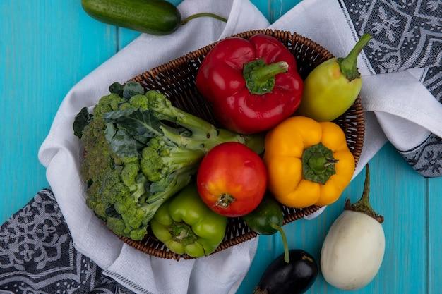 Draufsicht-tomate mit gurke und paprika mit brokkoli in einem korb auf einem küchentuch auf einem türkisfarbenen hintergrund Kostenlose Fotos