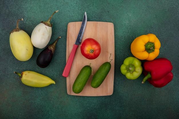 Draufsicht-tomate mit gurken auf einem schneidebrett mit einem messer und farbigen paprika-auberginen auf einem grünen hintergrund Kostenlose Fotos