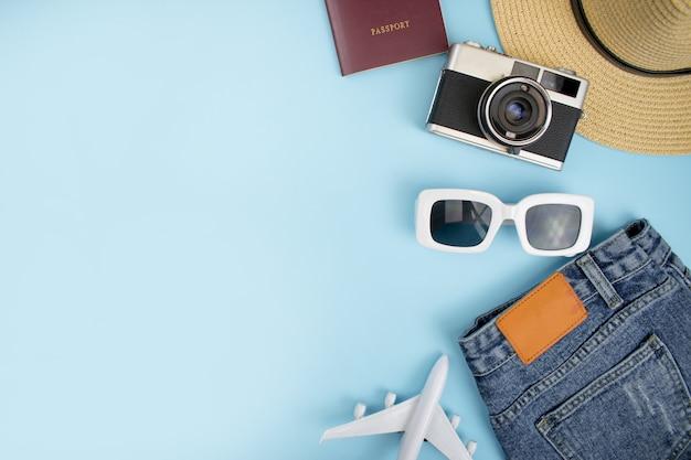 Draufsicht, touristisches zubehör mit jeans, filmkameras, pässen und hüten auf einem blauen hintergrund. mit copyspace. Premium Fotos
