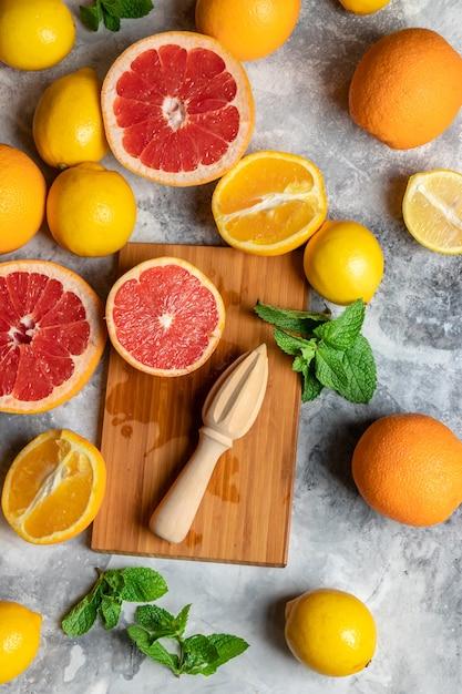 Draufsicht über mischung der neuen zitrusfruchtzusammensetzung mit orangen, zitronen, pampelmuse, minze und hölzernem schneidebrett und quetscher oder handpresse, mehrfarbiger abstrakter hintergrund für kopienraum Premium Fotos