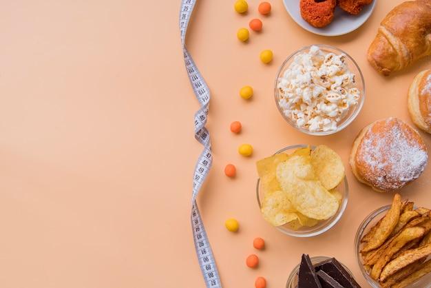 Draufsicht ungesunde snacks und maßband mit kopierraum Premium Fotos