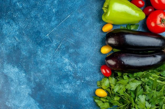 Draufsicht verschiedene gemüsekirschtomaten paprika-dill-auberginen-petersilie auf der rechten seite des blauen tischkopierplatzes Kostenlose Fotos
