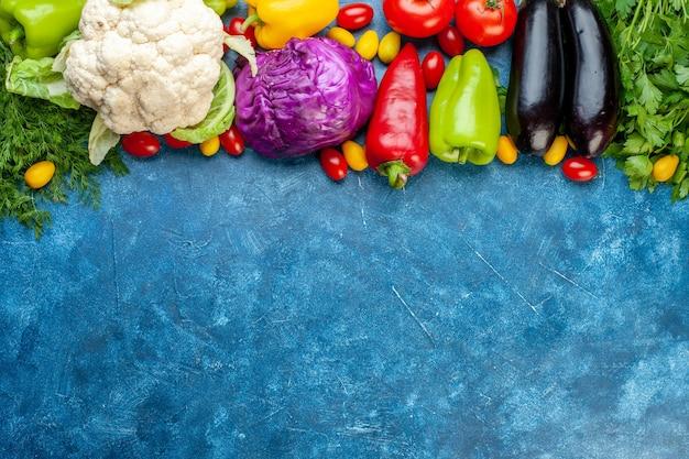 Draufsicht verschiedene gemüsekirschtomaten verschiedene farben paprika tomaten cumcuat auberginen blumenkohl rotkohl oben auf dem blauen tisch kopieren platz Kostenlose Fotos