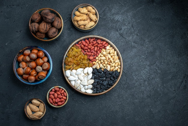 Draufsicht verschiedene nüsse mit rosinen und getrockneten früchten auf dunkelgrauem hintergrundnuss-snack haselnuss-walnuss-erdnüssen Kostenlose Fotos
