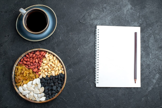 Draufsicht verschiedene nüsse mit rosinen und tasse kaffee auf der dunkelgrauen hintergrundnuss-snack-walnuss-erdnuss Kostenlose Fotos