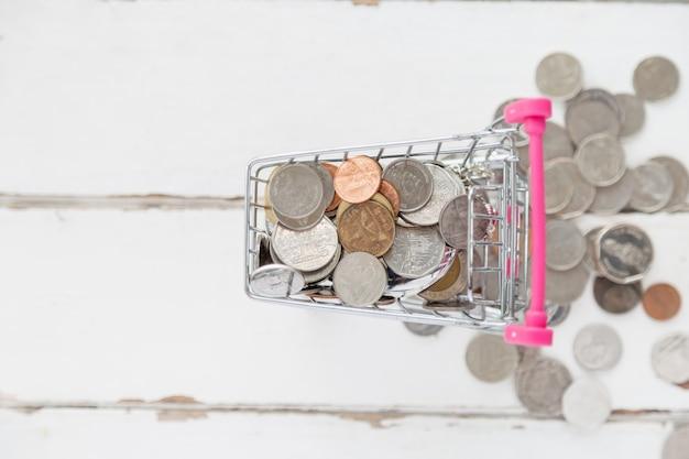 Draufsicht viele prägen im miniwarenkorb mit etwas münzentropfen vom warenkorb auf weißem bretterboden Premium Fotos