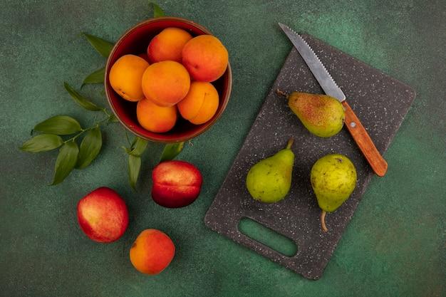 Draufsicht von aprikosen in schüssel mit muster von pfirsichbirnen mit messer und blättern auf schneidebrett und auf grünem hintergrund Kostenlose Fotos