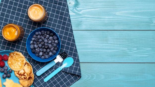 Draufsicht von blaubeeren mit babynahrung und anderen früchten Kostenlose Fotos