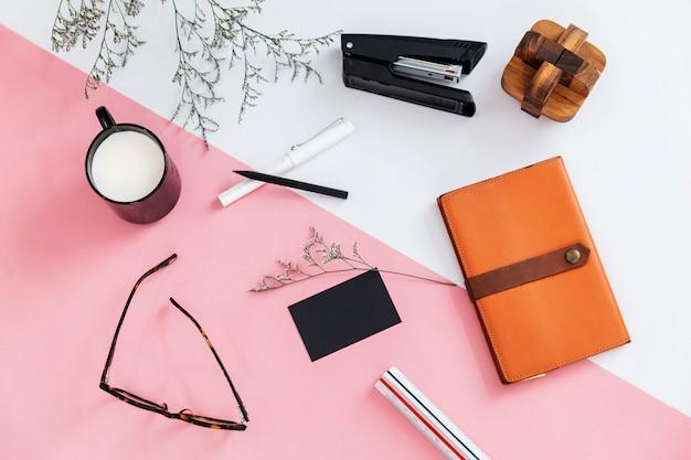 Draufsicht von blumenniederlassungen, eine schale milch, stift, bleistift, gläser, hefter, notizbuch Premium Fotos
