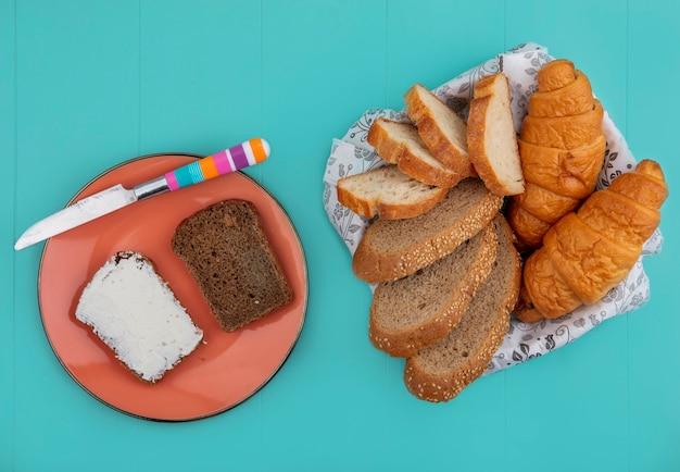 Draufsicht von broten als geschnittenes entkerntes cob-baguette und croissant in schüssel und roggenbrot verschmiert mit käse mit messer in platte auf blauem hintergrund Kostenlose Fotos
