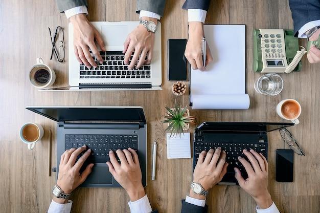 Draufsicht von coworking-leuten arbeiten an laptops und papierdokumenten. Premium Fotos