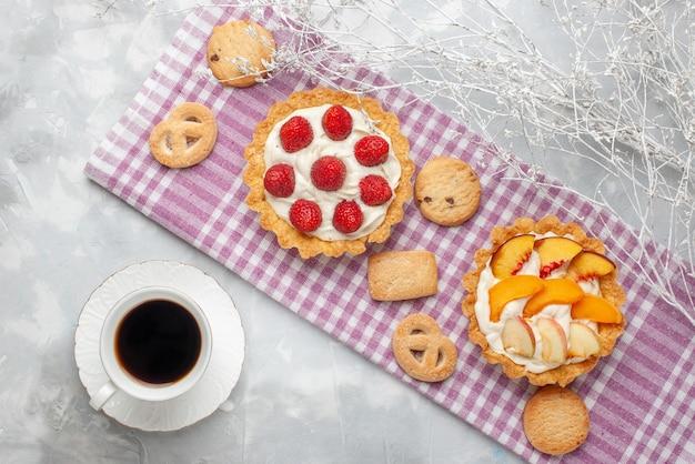 Draufsicht von cremigen kuchen mit weißer leckerer sahne und geschnittenen erdbeerenpfirsichen aprikosen mit keksen auf hellem schreibtisch, obstkuchencreme backen tee Kostenlose Fotos