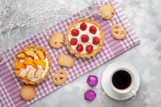 Draufsicht von cremigen kuchen mit weißer leckerer sahne und geschnittenen erdbeerenpfirsichen aprikosen mit keksen und tee auf hellem schreibtisch, obstkuchencreme backen Kostenlose Fotos