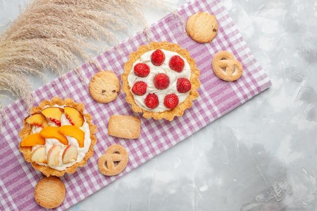 Draufsicht von cremigen kuchen mit weißer leckerer sahne und geschnittenen erdbeerpfirsichen aprikosen mit keksen auf hellem schreibtisch, obstkuchencreme backen Kostenlose Fotos