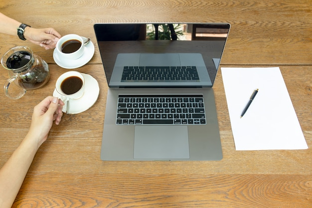 Draufsicht von den geschäftsmannhänden, die kaffeetasse mit laptop auf tabelle halten. Premium Fotos