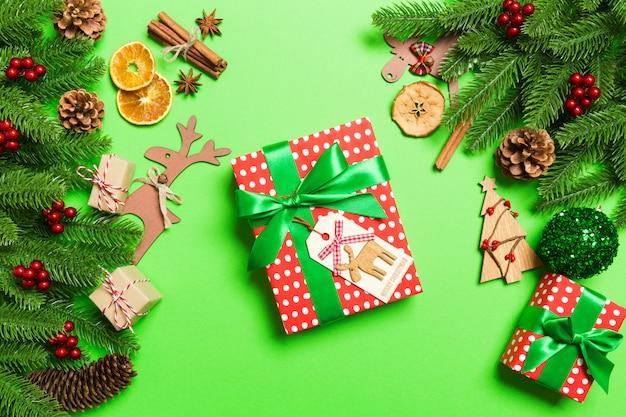 Draufsicht von den weiblichen händen, die ein weihnachtsgeschenk auf festlichem grün halten. Premium Fotos