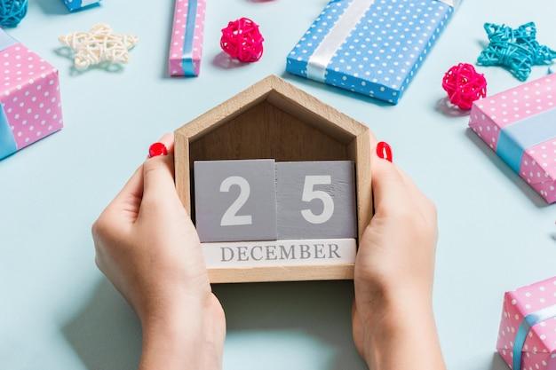 Draufsicht von den weiblichen händen, die kalender auf purpur halten. Premium Fotos
