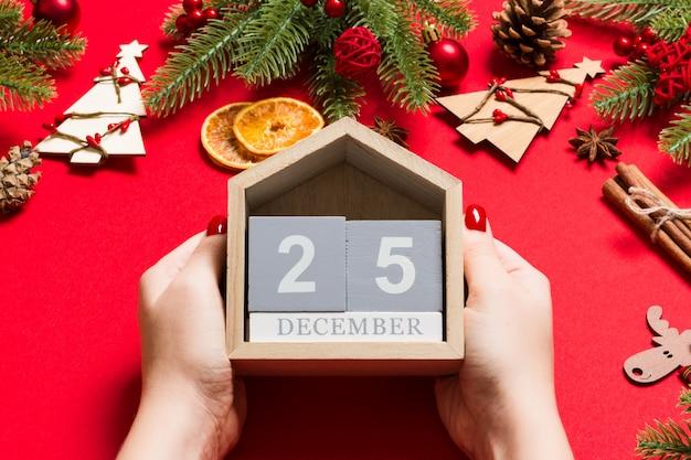 Draufsicht von den weiblichen händen, die kalender auf rotem hintergrund halten Premium Fotos