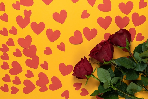Draufsicht von drei roten rosen liegen auf gelbem grund. viele pappherzen Premium Fotos