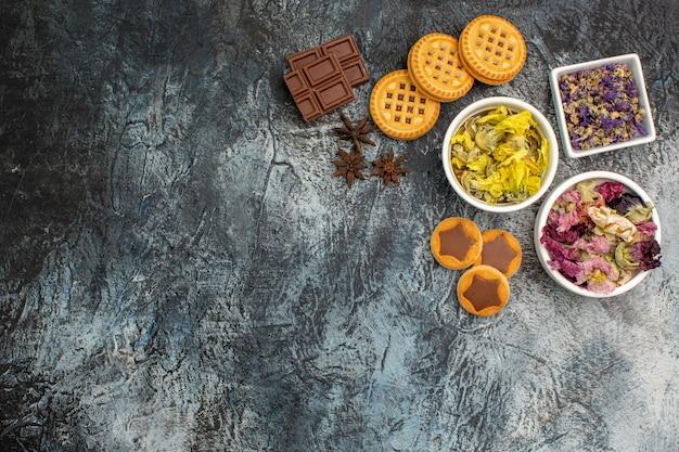 Draufsicht von drei schalen trockener blumen mit schokolade und keksen auf grauem hintergrund Kostenlose Fotos