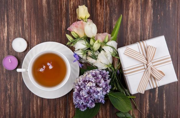 Draufsicht von frischen blumen wie gardenzia tulpenrosen mit einer tasse tee mit geschenkbox lokalisiert auf einem hölzernen hintergrund Kostenlose Fotos