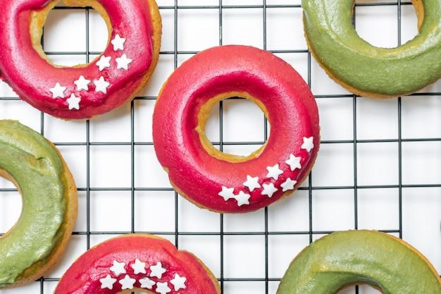 Draufsicht von frischen gebackenen schaumgummiringen mit heller rosa und grüner zuckerglasur Premium Fotos