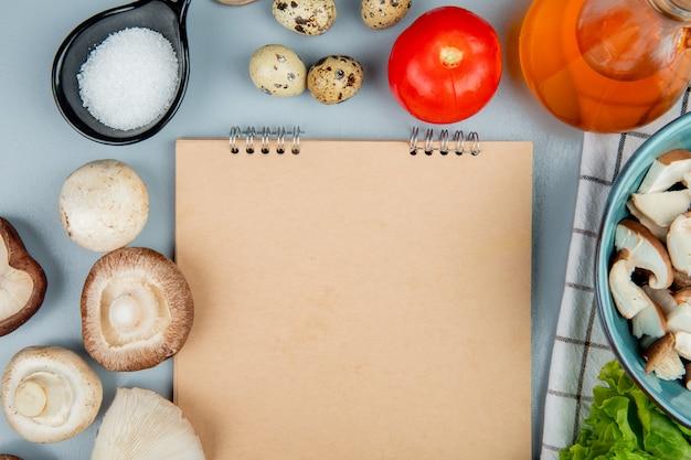 Draufsicht von frischen pilzen mit tomatenwachteleiern und salz angeordnet um ein skizzenbuch auf hellblau Kostenlose Fotos