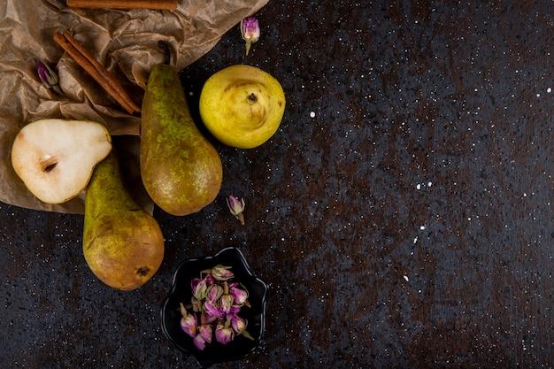Draufsicht von frischen reifen birnen mit einem stück bastelpapierzimtstangen und teerosenknospen auf schwarzem hintergrund mit kopienraum Kostenlose Fotos