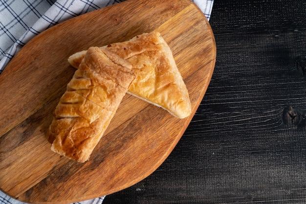Draufsicht von frischen süßen brötchen und von torte gesetzt auf einen hölzernen behälter und eine serviette zum morgenfrühstück. Premium Fotos