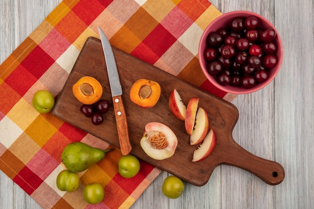 Draufsicht von ganzen geschnittenen und geschnittenen früchten als aprikosenpfirsichkirsche mit messer auf schneidebrett und kirschen in schüssel mit birne und pflaumen auf kariertem stoff auf hölzernem hintergrund Kostenlose Fotos
