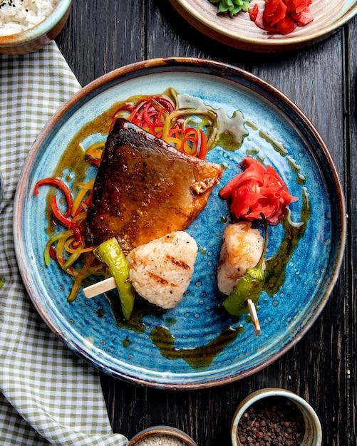 Draufsicht von geröstetem fisch mit gemüse eingelegten ingwerscheiben und sojasauce auf einem teller auf rustikalem Kostenlose Fotos