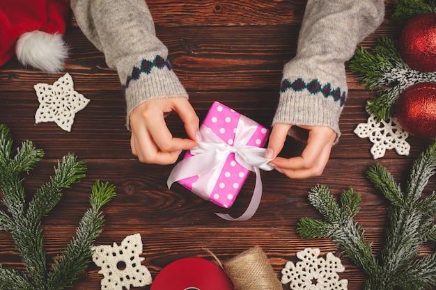Draufsicht von händen einer frau mit einem weihnachtsgeschenk auf hölzernem hintergrund Premium Fotos
