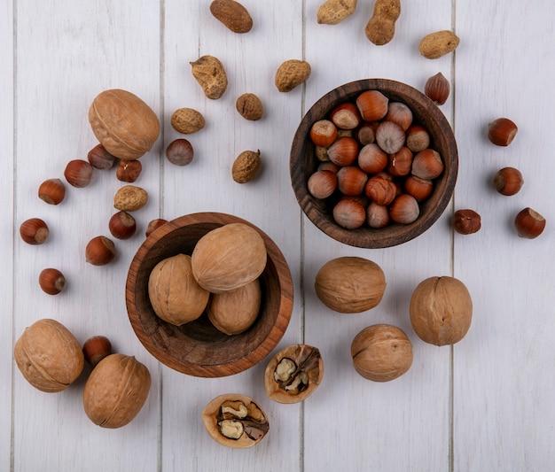 Draufsicht von haselnüssen mit walnüssen und erdnüssen in schalen auf einer weißen oberfläche Kostenlose Fotos