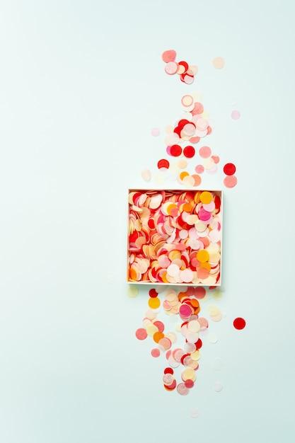 Draufsicht von hellen papierkonfettis in einem kasten auf pastellhintergrund. Premium Fotos