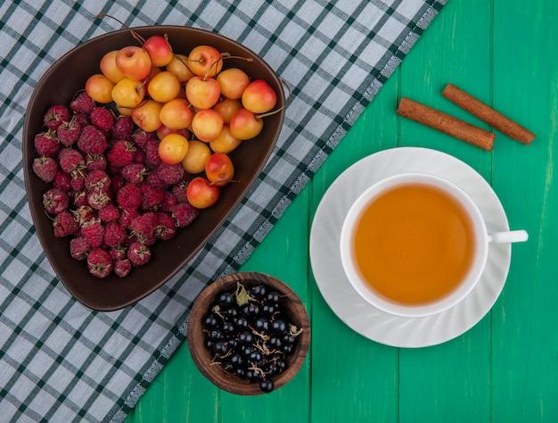 Draufsicht von himbeeren mit weißen kirschen in einer schüssel mit einer tasse teezimt und schwarzen johannisbeeren auf einer grünen oberfläche Kostenlose Fotos