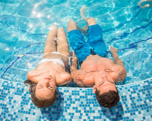 Draufsicht von jungen paaren entspannen sich im swimmingpool. Premium Fotos