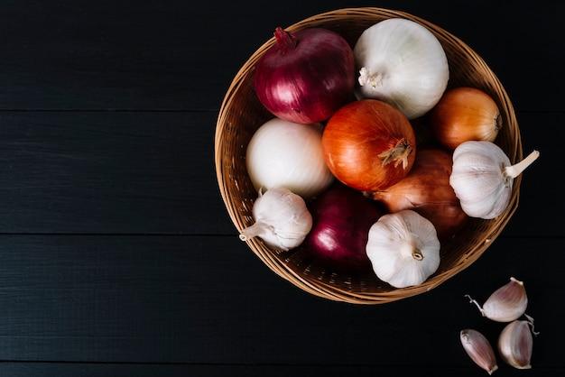 Draufsicht von knoblauchknollen und -zwiebeln im korb auf schwarzem hintergrund Kostenlose Fotos