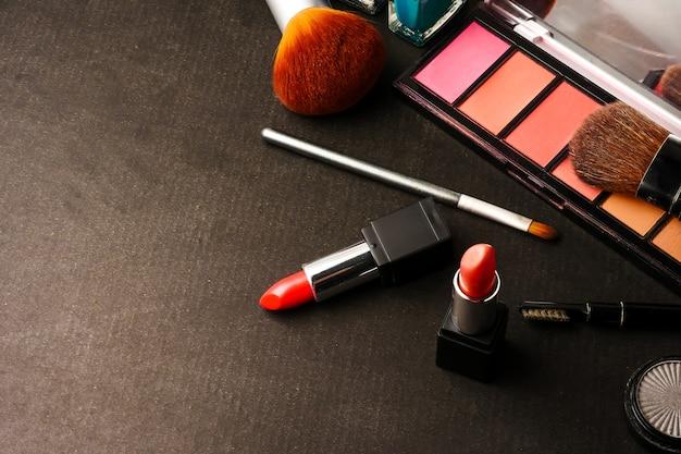 Draufsicht von kosmetik stellte für make-up auf einem schwarzen hintergrund ein. freier platz für text. Premium Fotos