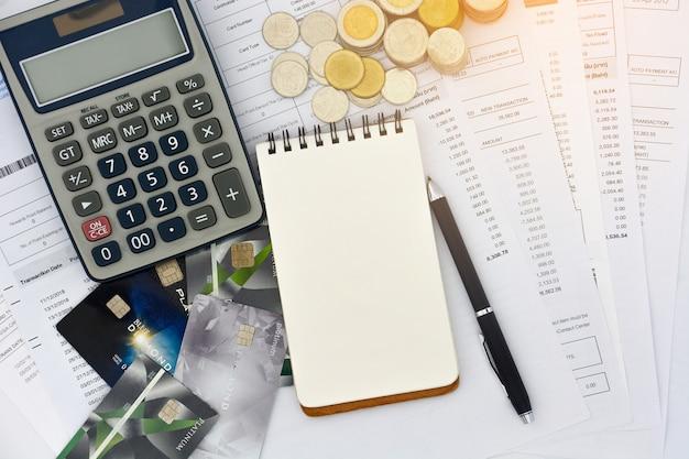 Draufsicht von kreditkarten mit aussagen, stift, leerem notizblock, stapel münzen und taschenrechner Premium Fotos