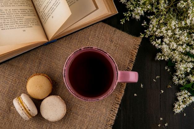 Draufsicht von macarons mit einer tasse tee auf einer beigen serviette mit einem offenen buch und blumen Kostenlose Fotos