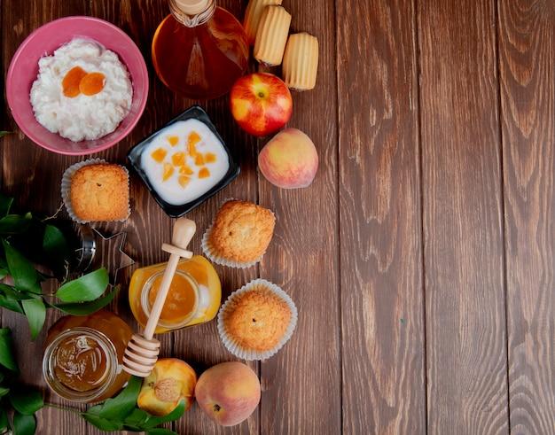 Draufsicht von marmeladengläsern als pfirsich und pflaume mit cupcakes pfirsiche hüttenkäse auf holzoberfläche verziert mit blättern mit kopierraum Kostenlose Fotos