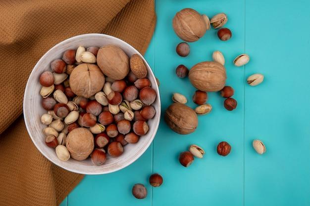 Draufsicht von mischnüssen in einer schüssel mit walnuss-haselnüssen mit pistazien mit einem braunen handtuch auf einer türkisfarbenen oberfläche Kostenlose Fotos