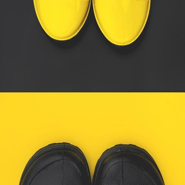 Draufsicht von modischen gummistiefeln der männer und der frauen auf kontrastierenden hintergründen. konzept des herbstes und der liebe. exemplar. Premium Fotos