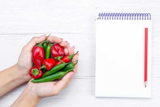 Draufsicht von paprika würzig halten von frau mit notizblock auf leichtem, gemüse scharfem essen mahlzeit roh Kostenlose Fotos