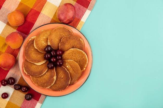 Draufsicht von pfannkuchen mit kirschen in platte und aprikosen auf kariertem stoff auf blauem hintergrund mit kopienraum Kostenlose Fotos