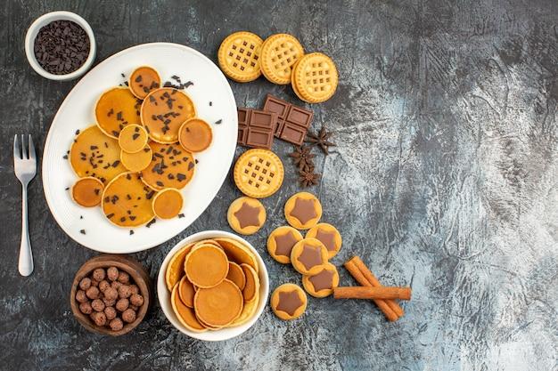 Draufsicht von pfannkuchen und verschiedenen arten von desserts auf grauem hintergrund Kostenlose Fotos